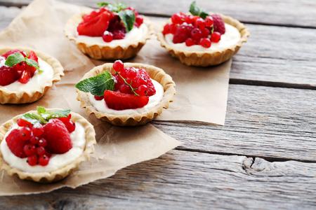 Dessert tartlets with berries on grey wooden background