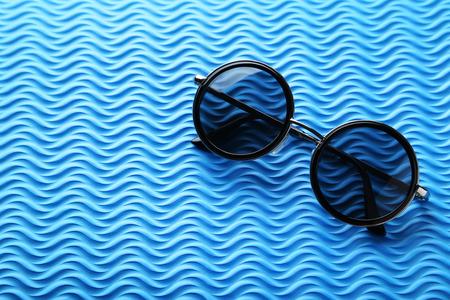 Black sunglasses on the blue background