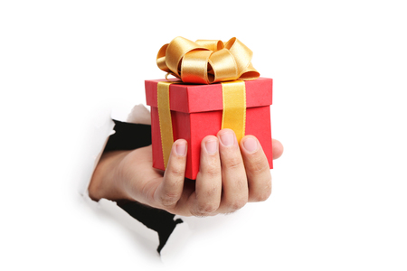 Male hand with gift box punching through the paper Stock Photo