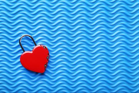 Heart shaped padlock on blue background Stock Photo