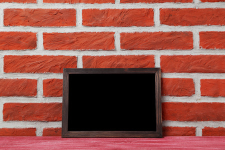 Wooden frame on a brick wall background