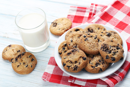 Chocolate chip cookies with glass of milk on white wooden table Stock Photo