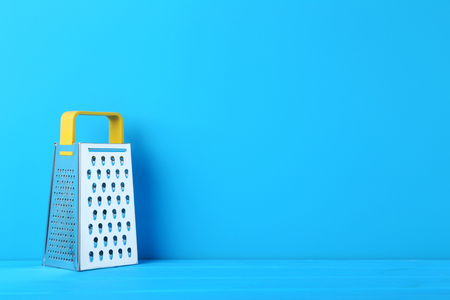 Metal grater on the blue wooden table Stock Photo