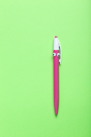 Pen with googly eyes on a green background Stock Photo