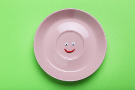 Pink plate with googly eyes on a green background Stock Photo