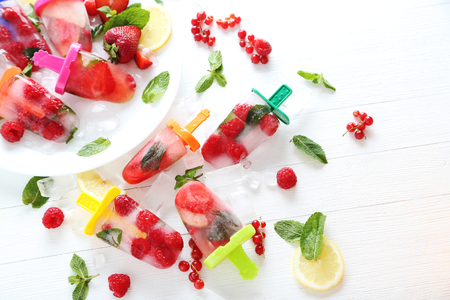 Popsicles with berries on white wooden table Stock Photo