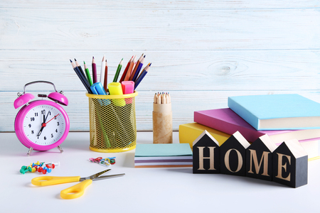 Pencils and felt-tip pens with books on colourful wooden wall Stock Photo