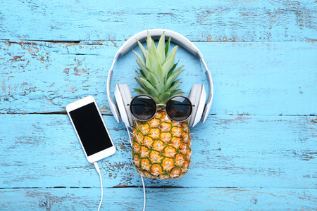 Ripe pineapple with headphones and smartphone on blue wooden table