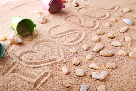 inscriptions: Words written on beach sand with stones and buckets Stock Photo