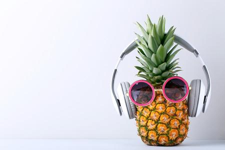 灰色の背景の上にヘッドフォンと熟したパイナップル