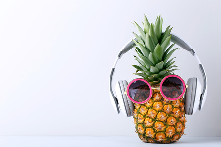 Ripe pineapple with headphones on grey background