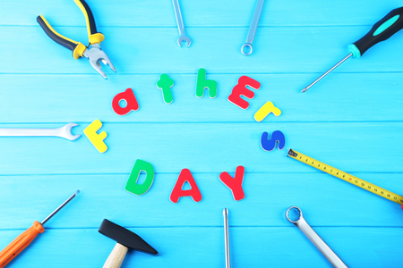 Different tools for fathers day on blue wooden table