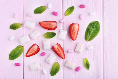 whiten: Chewing gums with mint leafs and strawberries on wooden table
