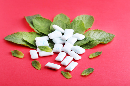Chewing gums with mint leafs on red background Stock Photo