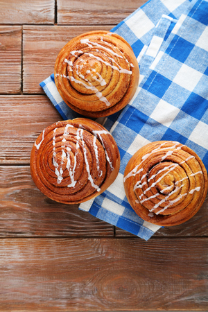 cinnamon swirl: Cinnamon buns with napkin on wooden table
