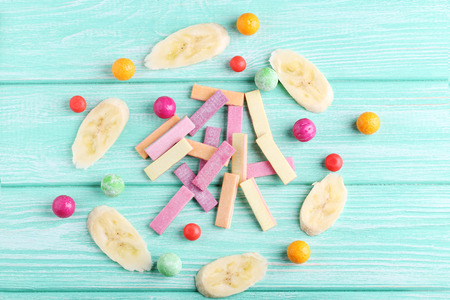 Different chewing gums with banana on mint background