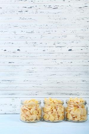 Cornflakes in glazen pot op houten tafel