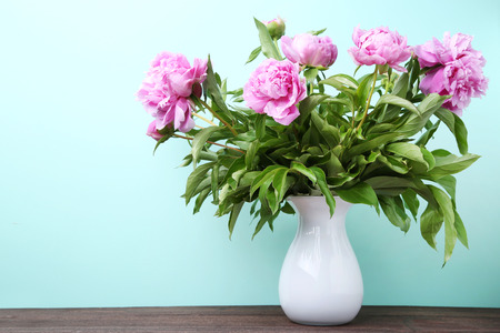 Bouquet of peony flowers in vase on mint background Stock Photo - 81067168