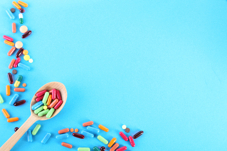 Colorful capsules in wooden spoon on blue background