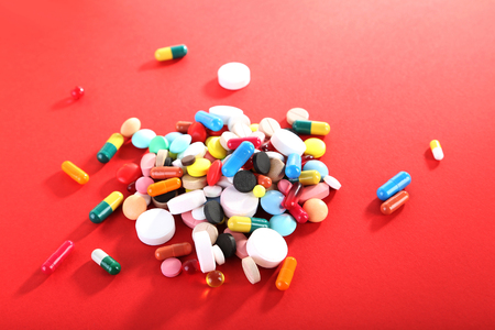 Different colorful pills on red background Stok Fotoğraf - 81067205