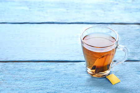 Cup of tea with teabag on blue wooden table