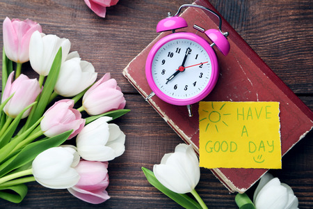 alarmclock: Bouquet of tulips with alarm clock on brown wooden table