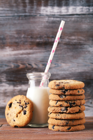 Chocolate chip cookies with bottle of milk on brown wooden table 版權商用圖片