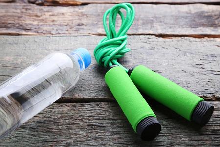 saltar: Cuerda verde que salta con la botella de agua en la tabla de madera