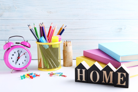 Stationery with alarm clock and books on wooden table Stock Photo