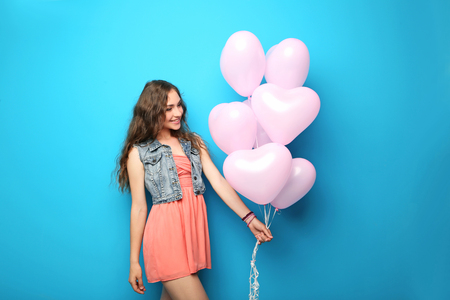 Portrait of young woman with pink heart balloon on blue background