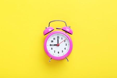 alarmclock: Pink alarm clock on the yellow background