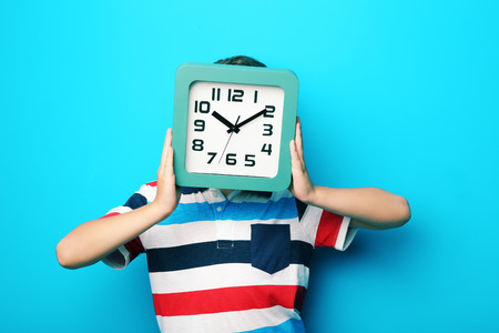 antics: Young boy with clock on blue background Stock Photo