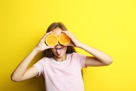 Retrato de una chica hermosa con fruta naranja sobre fondo amarillo Foto de archivo