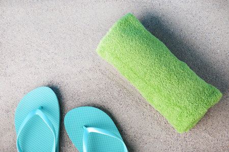 Pair of flip flops with green towel on the beach sand