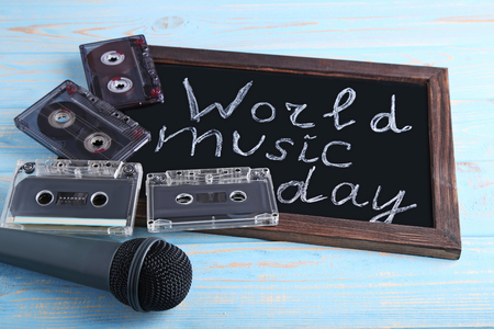 Inscription World Music Day with microphone and cassette tapes on blackboard