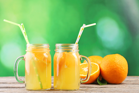 Glass jars with orange juice on wooden table