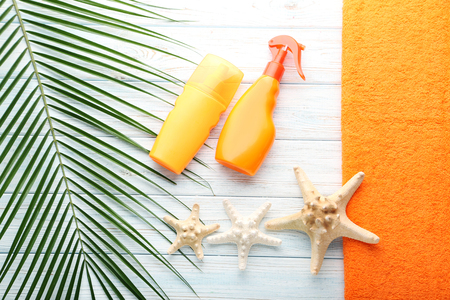 Sunscreen with starfish on wooden table Stock Photo