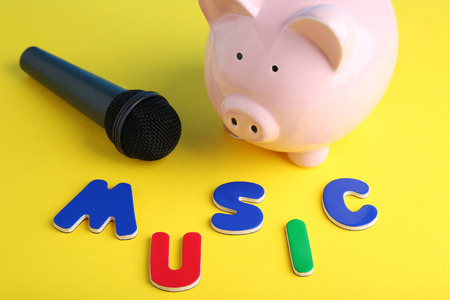 Black microphone with piggybank and inscription Music Stock Photo