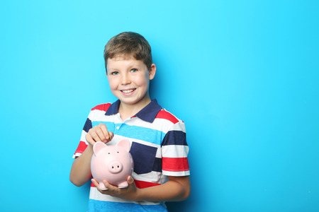 antics: Portrait of young boy with piggy bank on blue background