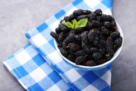 Black mulberries in bowl with napkin on wooden table
