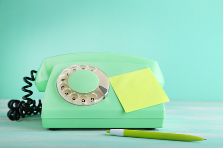 Green retro telephone with sticky note and pen on wooden table Stock Photo