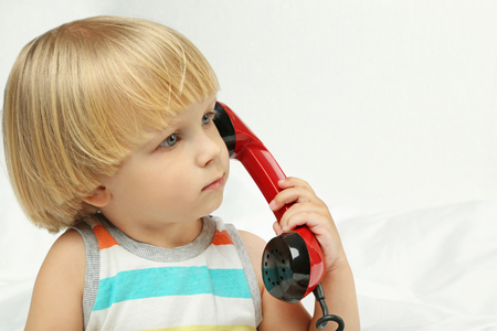 Little boy with handset on white background
