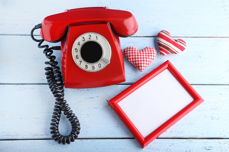 Red retro telephone with photo frame and hearts on white wooden table Stock Photo