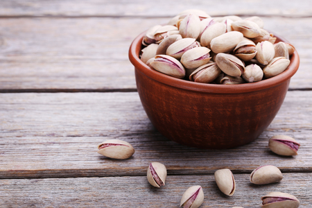 Heap of pistachios in bowl on wooden table Stock Photo