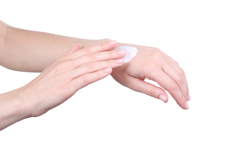 Female hand with sunscreen cream on hand on white background
