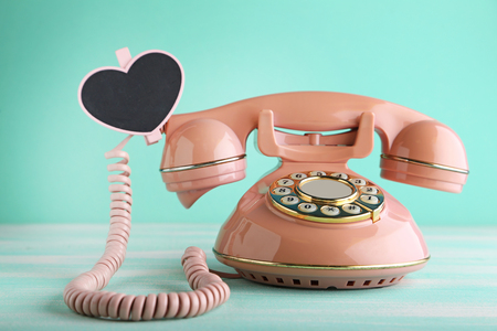 Pink retro telephone with heart on green wooden table