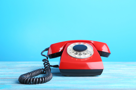 phone cord: Red retro telephone on wooden table