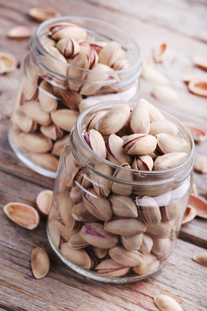 nutshells: Heap of pistachios in bottles on wooden table Stock Photo