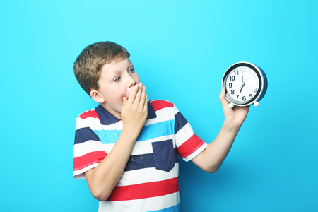 antics: Portrait of emotional boy with round clock on blue background
