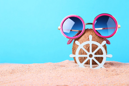 b56e1fc9fde  83250081 - Coconut with sunglasses and ship wheel on beach sand